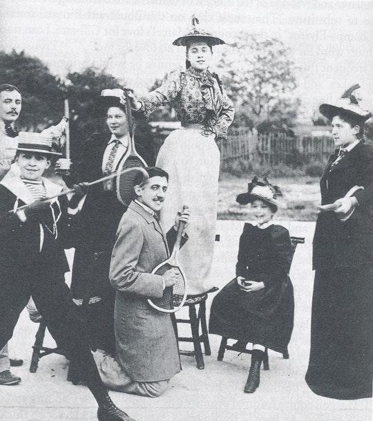 Grupo de pessoas posa para foto com Proust de joelhos fingindo tocar uma raquete de tênis como se fosse uma guitarra. Fonte