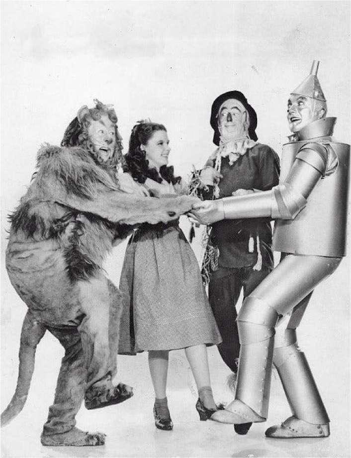 Judy Garland e os companheiros de Oz em um still publicitário da época.