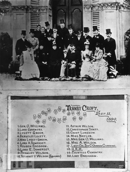 """O elenco de jogadores envolvidos no """"Escândalo real do bacará"""". Foto tirada em Tranby Croft, na casa de campo de sir Arthur Wilson. Entre os retratados estão: sir William Gordon-Cumming (1848-1930); Lycett Green e esposa; o capitão Berkeley Levett, da Guarda Escocesa; sir Arthur Wilson e a sra. Wilson; lorde Coventry; lorde Somerset; e S.A.R. Eduardo, príncipe de Gales, mais tarde rei Edward VII da Inglaterra - Fonte."""